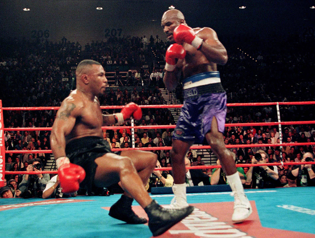 Challenger Evander Holyfield (R) knocks down WBA heavyweight champion Mike Tyson during the 6th round of their title fight November 9, 1996 in Las Vegas. Holyfield won the championship with an 11th round TKO. REUTERS/Gary Hershorn PP05060142  GMH/CMC Reuters / Picture supplied by Action Images *** Local Caption *** RBBORH1996110900001.jpg
